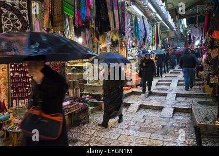 Israel, Jerusalem, Visitors in tourist market on rainy day; Jerusalem Old City - Stock Photo