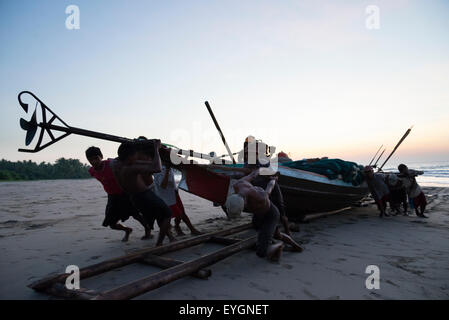 Myanmar (Burma), Irrawaddyi division, Fishermen pulling their boat ashore; Yea Thoe village - Stock Photo