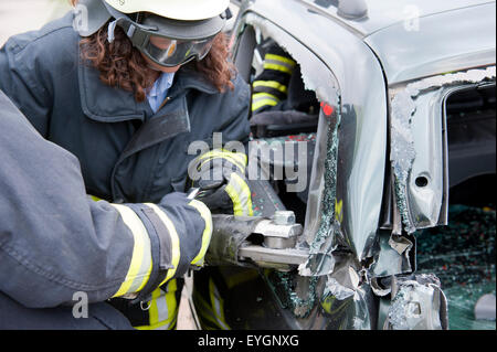 Rescue operation of the fire brigade on a car Germany Europe - Stock Photo