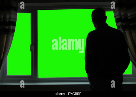 Chroma-key silhouette of a senior man back to camera, looking out of a window. Space for your own background.