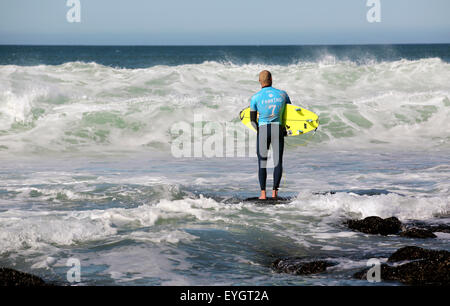 Australian professional surfer Mick Fanning entering the water at the 2015 J-Bay Open surfing event in Jeffreys - Stock Photo