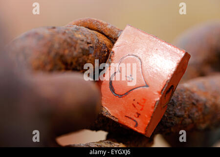 An old weathered love lock attached to a rusty old chain. the lock has a heart shape carved into its body and initials - Stock Photo