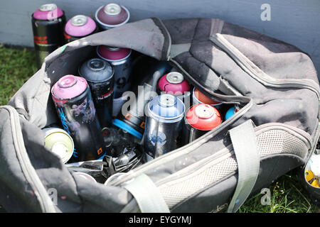 A group of used Kobra graffiti artists spray cans left under a small platform a graffiti artist is currently using - Stock Photo