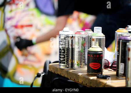 A group of used Kobra graffiti artists spray cans left on a table at the Bristol Upfest event. A blurred working - Stock Photo