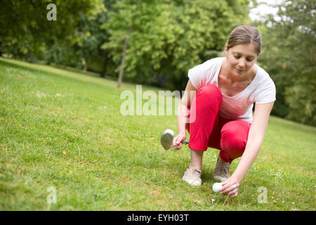 young woman placing a golf ball on a tee. - Stock Photo