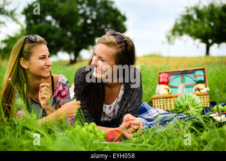 Best friends - two attractive young girls are having a picnic, dressed casual lying on the lawn in summer and chatting - Stock Photo