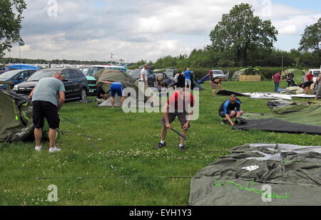 Random people putting up tents in a field - Stock Photo