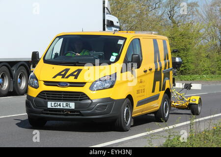 A 2014 AA BREAKDOWN RESCUE YELLOW VAN DRIVING ALONG A MAIN A ROAD WITH A TRAILER CARRYING A MOTORCYCLE - Stock Photo