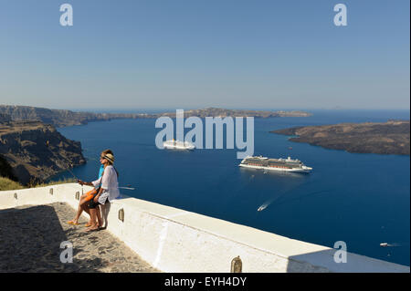 A young couple taking a Selfie photograph of themselves two with cruise ships in the distance, Santorini, Greece.