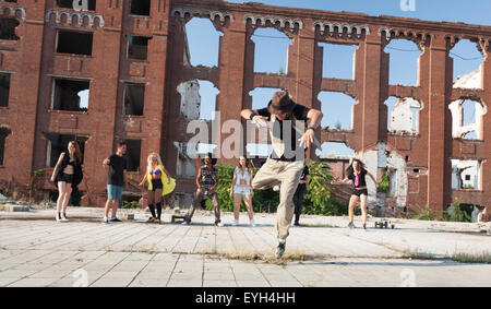 Energetic young hip hop street dancer performing his routine in an urban square watched by his gang. - Stock Photo
