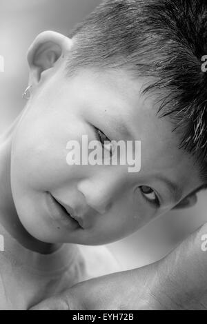 Portrait of a little mongoloid boy happy and innocent with copy space, curious look in the eyes - Stock Photo