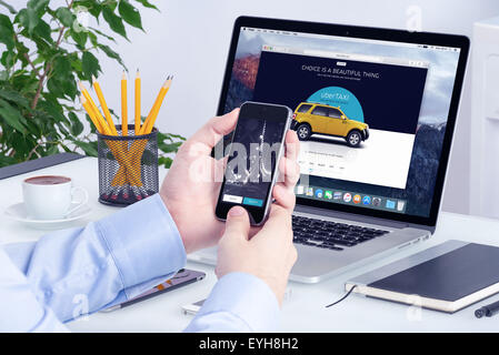 Varna, Bulgaria - May 29, 2015: Uber application on Apple iPhone display and desktop version of Uber on Apple Macbook - Stock Photo