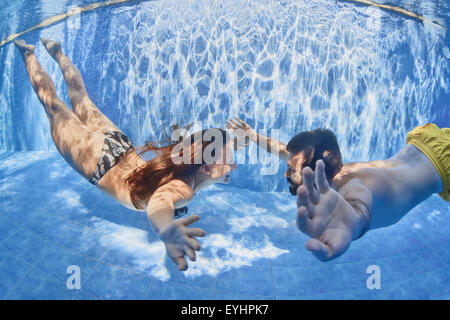 Happy newlywed family having fun on tropical honeymoon holidays - positive couple swimming and diving underwater - Stock Photo