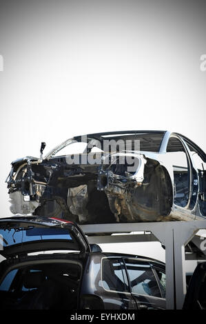 Vignetted photo of wrecked vehicles in a car junkyard - Stock Photo