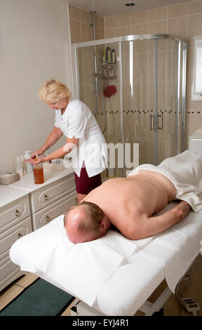 Masseuse preparing oil for her client who is to receive a massage in the treatment room - Stock Photo