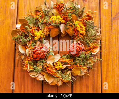 Autumn wreath with dried flowers against a wooden background - Stock Photo