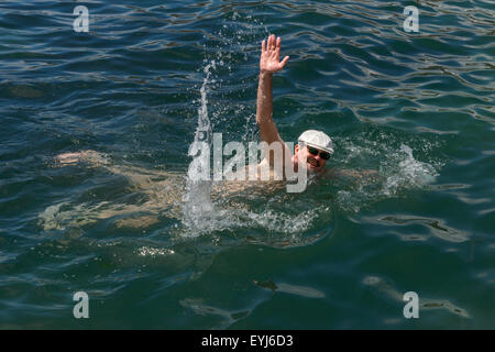 High angle view of mature man that raised his hand I salute with splashing while swimming in sea water. - Stock Photo