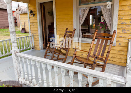 A pair of old wooden rocking chairs sit on the painted wooden porch of a faded yellow country house. - Stock Photo