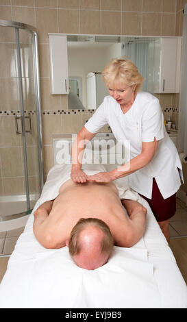Masseuse working with a male client Providing a relaxing back massage - Stock Photo