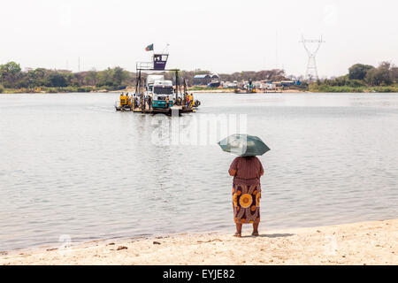 Local woman with umbrella waits for the approaching Kazungula Ferry, a pontoon ferry over the Zambezi River crossing - Stock Photo