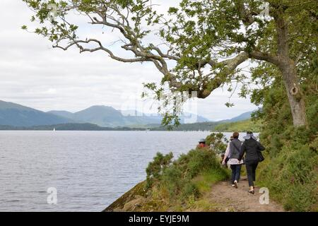 Tourists take in the view whilst walking along the well worn loch side path at Loch Lomond, Scotland, UK - Stock Photo