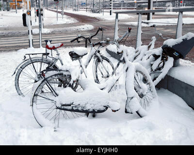 Snow covered bicycles in Amsterdam - Stock Photo