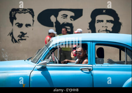 HAVANA, CUBA - JUNE, 2011: Pedestrians and classic American cars pass in front of stencil billboard featuring Communist - Stock Photo