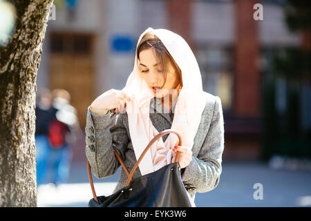 girl looking for something in a bag - Stock Photo
