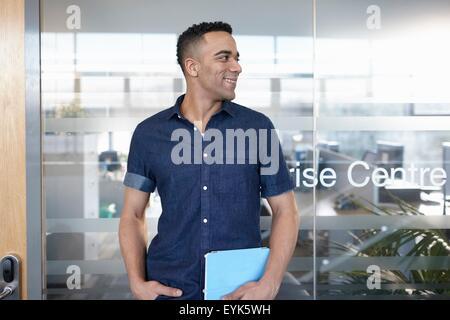Portrait of businessman at office door - Stock Photo