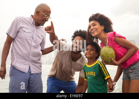 Grandfather and family looking up from Ipanema Beach, Rio De Janeiro, Brazil - Stock Photo