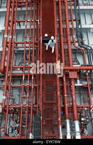 Workers walking along walkway at shipping port, elevated view, GoSeong-gun, South Korea - Stock Photo