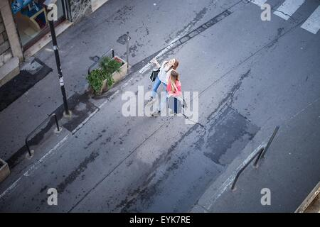 High angle view of two female friends laughing whilst strolling on city street - Stock Photo