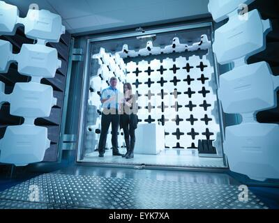 Engineers reviewing test results in laboratory in an anechoic chamber used for electromagnetic compatibility testing - Stock Photo