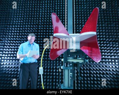 Engineer in anechoic chamber with horn antenna set up for electromagnetic compatibility (EMC) radiated emission - Stock Photo