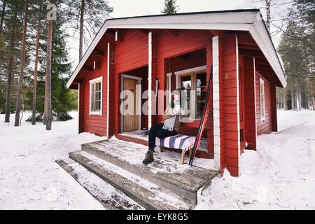 Portrait of young female skier drinking coffee on cabin porch, Posio, Lapland, Finland - Stock Photo