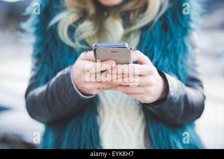 Close up of young woman texting on smartphone, Lake Como, Como, Italy - Stock Photo