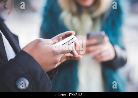 Close up of two young women texting on smartphones, Lake Como, Como, Italy - Stock Photo