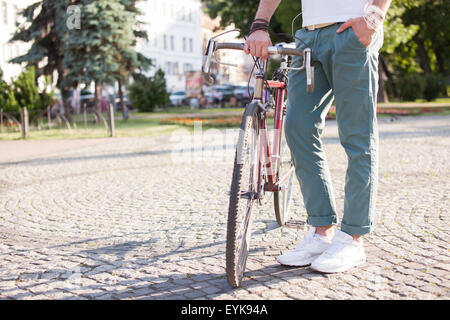 Stylish guy holding vintage race bike - Stock Photo