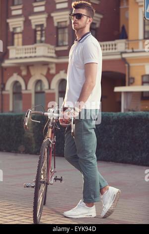 stylish biker with vintage race bike - Stock Photo