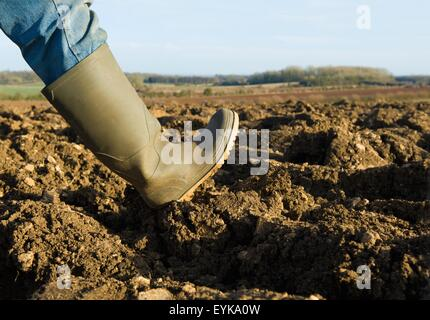 Close up of farmers rubber boot walking on ploughed field - Stock Photo