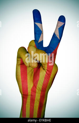 the hand of a young man giving the V sign patterned with the Estelada, the Catalan pro-independence flag - Stock Photo