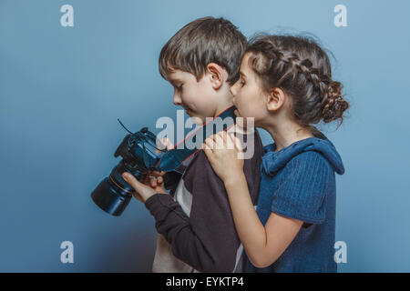 Teenage boy with a girl  watching pictures on the  camera - Stock Photo