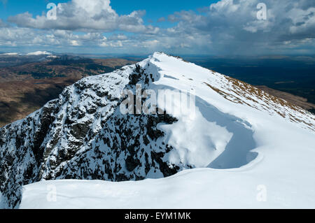 Snow cornices and drifts on the summit ridge of Ben Lomond, Stirlingshire, Scotland, UK, after heavy a spring snowfall. - Stock Photo