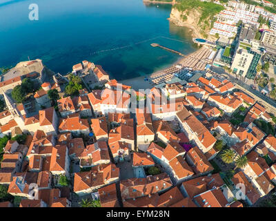 View of old town Budva from the top: Ancient walls and tiled roof of old town Budva, Montenegro, Europe. Aerial - Stock Photo