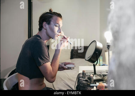 Male drag queen putting on make up and dressing up in prepration for a performance - Stock Photo