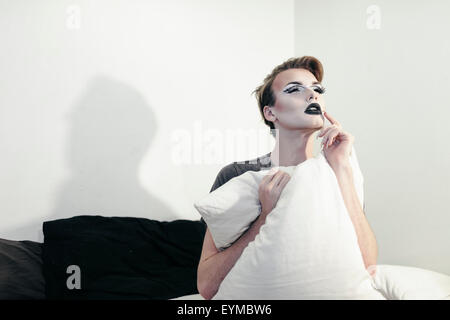Male drag queen posing for pin-up style glamor portrait at home.