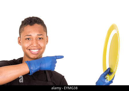 Hispanic young man wearing blue cleaning gloves holding up yellow plate and smiling to camera - Stock Photo