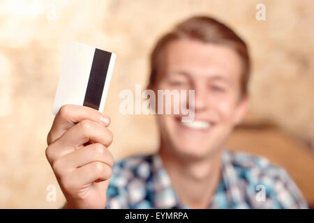 Smiling man showing his credit card - Stock Photo