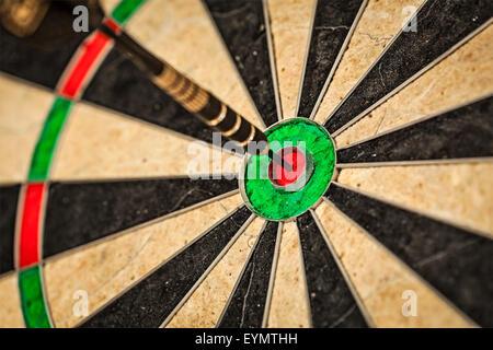 Success hitting target aim goal achievement concept background - dart in bull's eye close up - Stock Photo