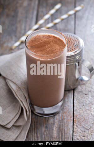 Cold chocolate milkshake in tall glass with ice - Stock Photo